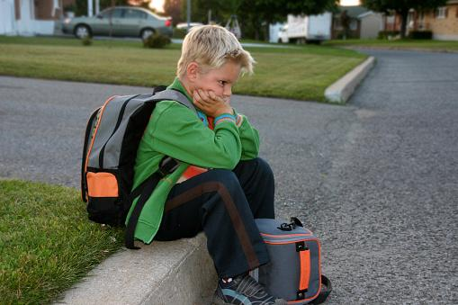 Young boy sitting on curb