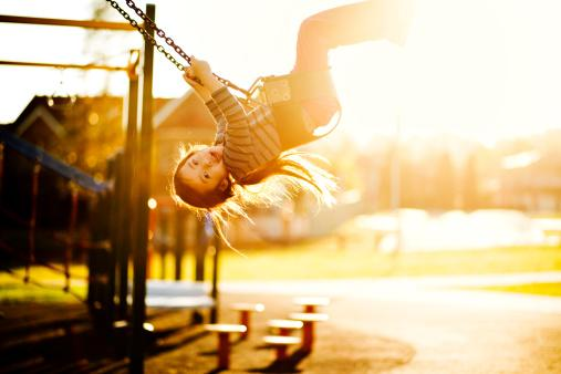 little girl happily swinging