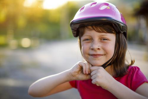 girl putting on helmet