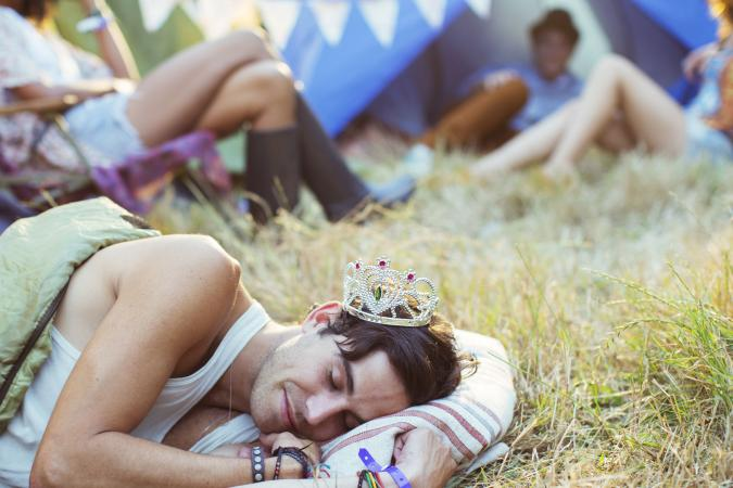 Man in tiara sleeping in sleeping bag