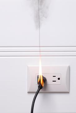 Cable plugged into wall catching fire