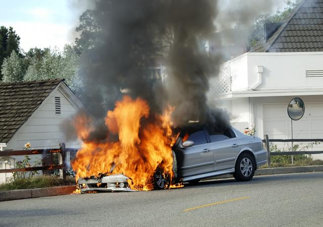 Silver car with front end burning