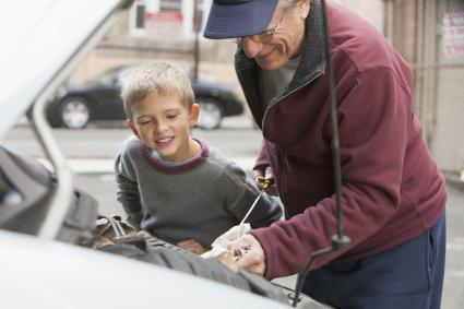 man with grandson checking oil in car