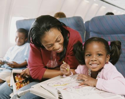 Mom and daughter on plane trip coloring in book