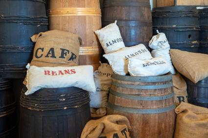 Cafe, beans, almonds, oat bags sitting on barrels in warehouse