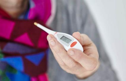 Woman holding digital thermometer