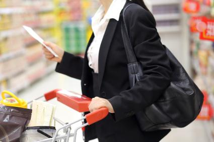 Woman holding shopping list while going through aisles