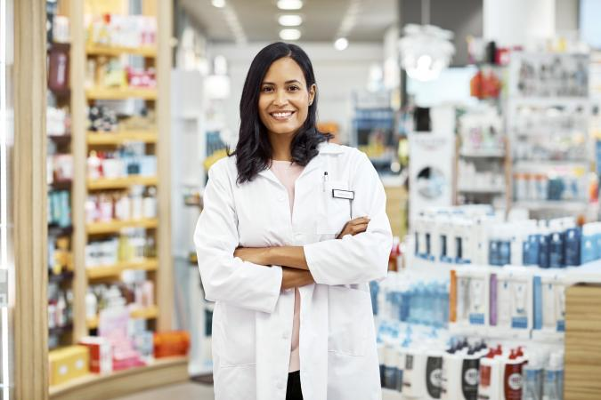 Pharmacist standing with arms crossed at pharmacy