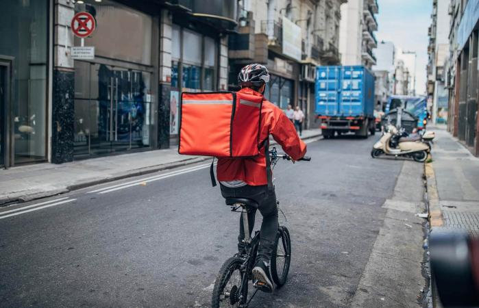 Delivery boy on bicycle in city