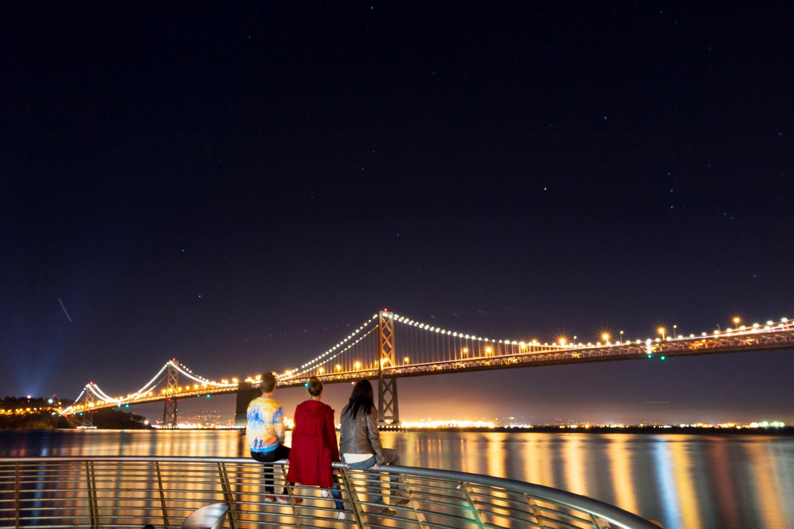 People Sitting On Railing Against Illuminated Bay Bridge At Night