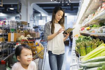 Mom grocery shopping with open tablet