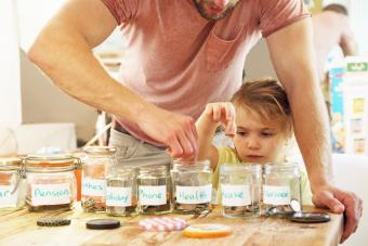 Father teaching daughter about finances by putting coins in jars