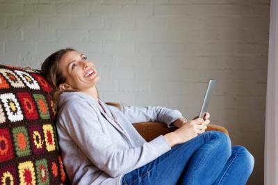 Woman laughing at tablet