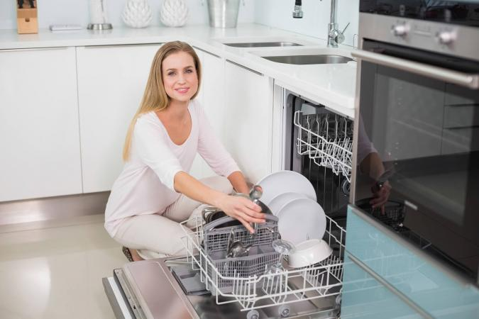 Woman kneeling behind dish washer