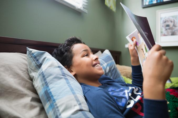 Boy reading magazine in bed