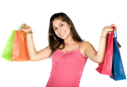 Happy fashionista holding up shopping bags