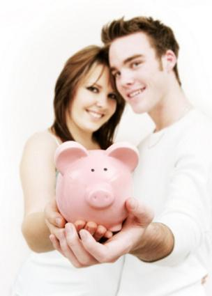 Young couple holding pink piggy bank