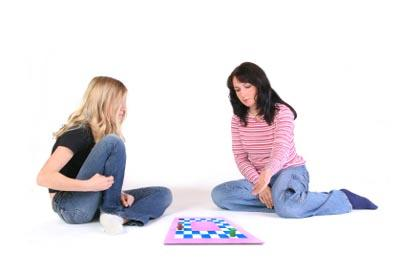 Two teen girls playing a board game