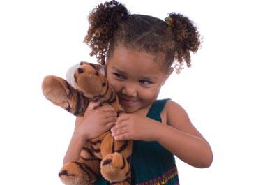 Little girl hugging stuffed tiger toy