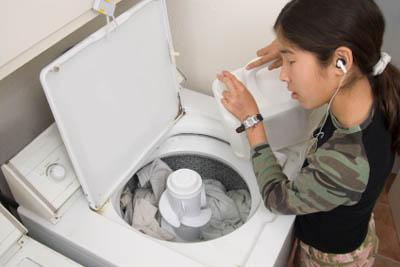 Teen adding detergent to laundry