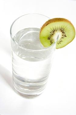 Glass of filtered water with a kiwi slice