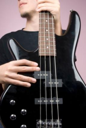 Young man holding an electric bass guitar