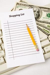 Shopping list and money on computer keyboard