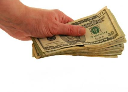 Image of a hand holding thick stack of cash