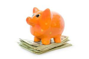 Piggy bank standing on a stack of money
