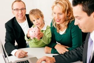 Family with advisor around computer; girl with piggy bank