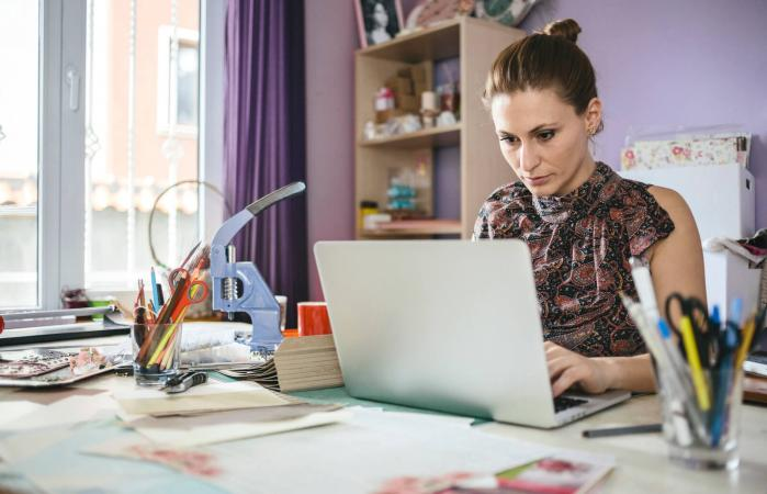 woman using laptop to scrapbook