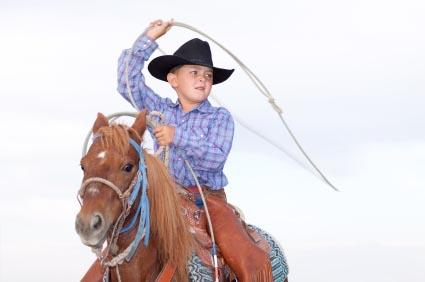 Young cowboy with lasso on horse.