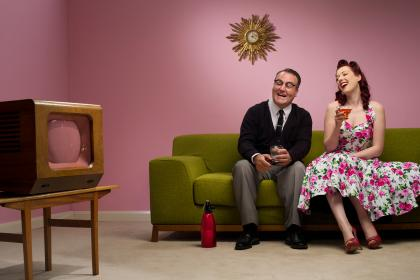 Retro couple with tv and laughing