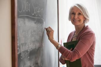 Teacher writing on chalkboard