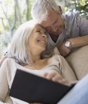 Flirty senior couple snuggling at home