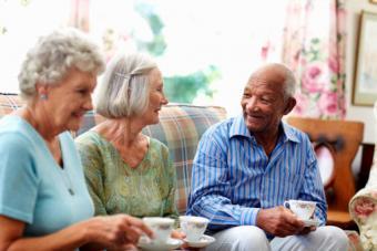 Three senior people having coffee