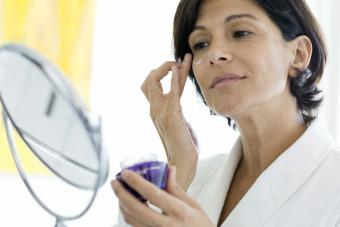 Woman in robe applying eye cream