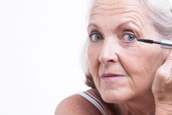 Mature woman applying eye makeup