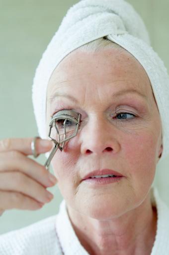 Senior woman using eyelash curler