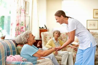 Nurse holding senior woman's hand