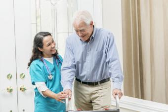 Home healthcare worker helping elderly man with walker