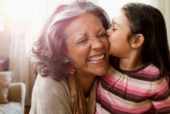Granddaughter kissing her grandmother's cheek
