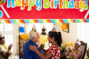 Family celebrating senior man birthday in nursing home