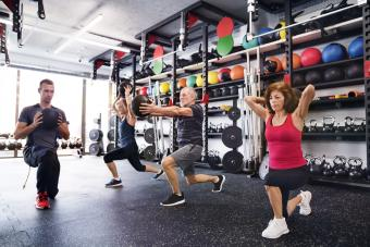 Seniors with personal trainer in gym exercising