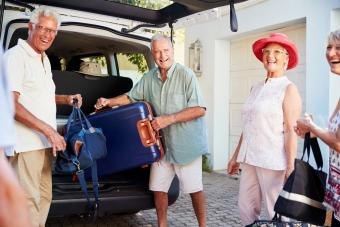 Group Of Senior Friends Loading Luggage Into Trunk Of Car