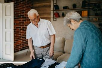 Senior couple laughing while packing suitcases