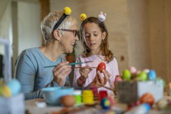 Senior woman and child decorating Easter eggs
