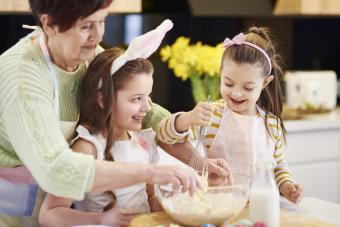 Grandmother and her two granddaughters making Easter cookies