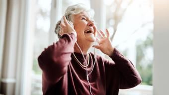 Happy senior woman listening to music with headphones