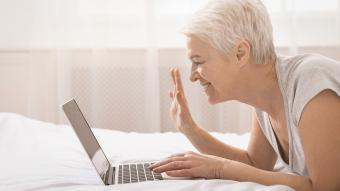 Cheerful grandmother talking with relatives via laptop onlin